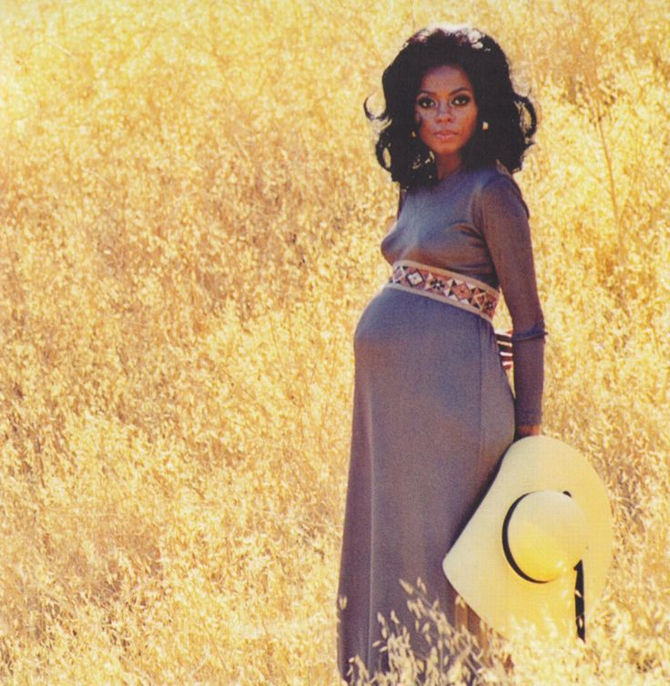 A pregnant Diana Ross wearing a maxi dress with a wide-brimmed hat