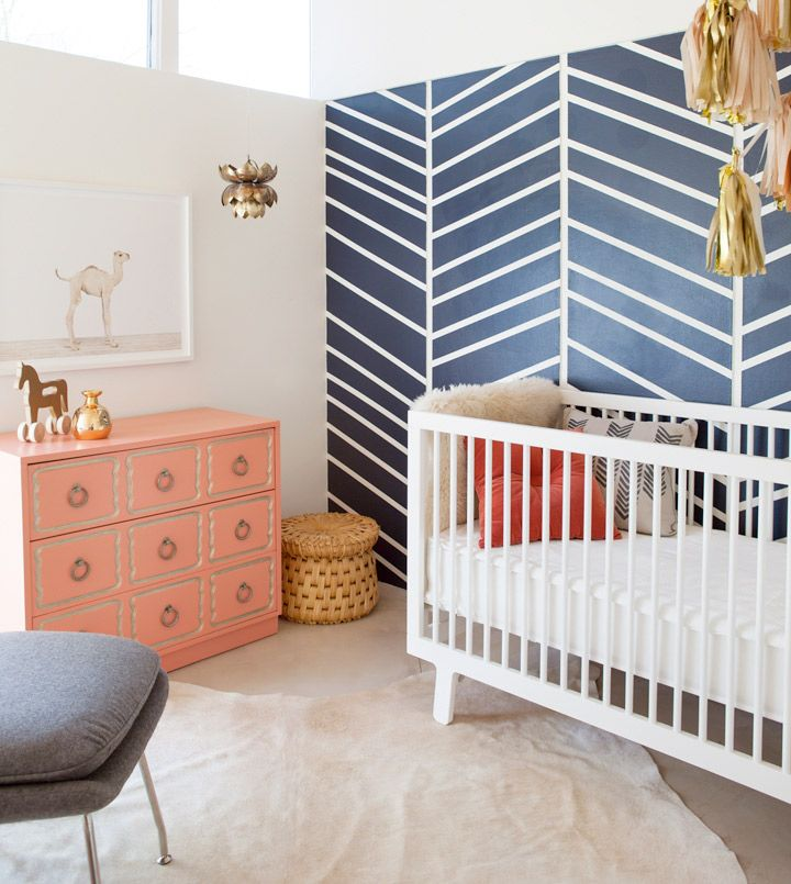 Unisex nursery with blue pattern on the walls, salmon traditional dresser and wicker laundry basket