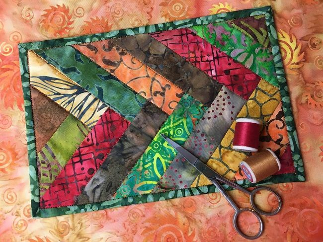 Put a charm square of batiks to good use with this free mug rug pattern, featuring a complicated-looking braided quilt top.