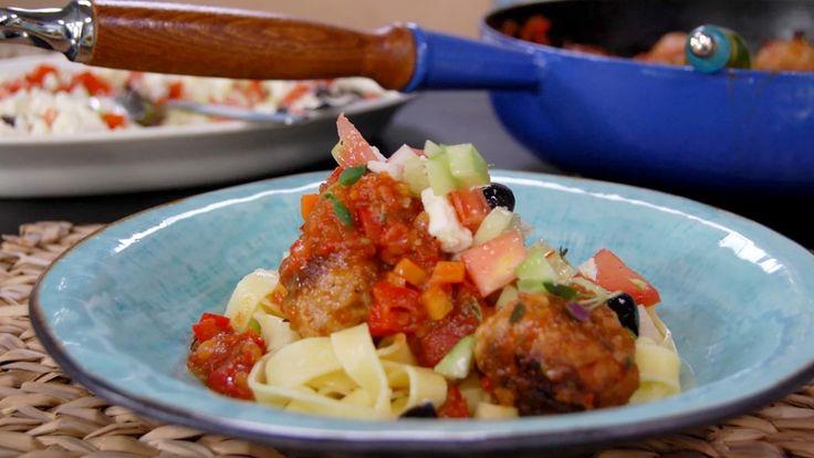 Kjøttboller av lam i tomatsaus serveres med gresk salat og tagliatelle.