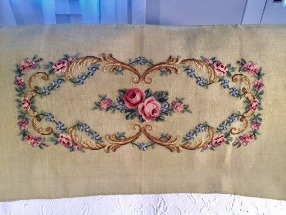 Floral preworked wool needlepoint. This is bench size  Roses and embellishments Pinks,some blue,some light purple, greens, and tans  Size of the canvas is approximately 45 inches by 23 1/2 inches. The needlepoint measures approximately 29 inchesby 12 1/2 inches.  The canvas is in very good condition - no holes.