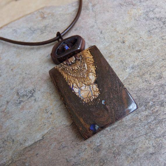 Boulder Opal Schmuck wie es sehr oft nicht angezeigt wird... Naturen tragbare Kunst vom Feinsten. Boulder Opal trifft eine Eisen-Stein-Höhle, die eine kleine lebendige lila Opal beherbergt.  Ein Schmuckstück Aussage bin ich in Ehrfurcht mit! Eine atemberaubende Halskette für alle Liebhaber der einzigartigen, großen und sicherlich ungewöhnlich. Zeigen Sie die Schönheit der Natur-Kunst.  Ein großes Quadrat schneiden Boulder Opal, die ein kleines transluzentes opalized Stück Holz in der Ecke…