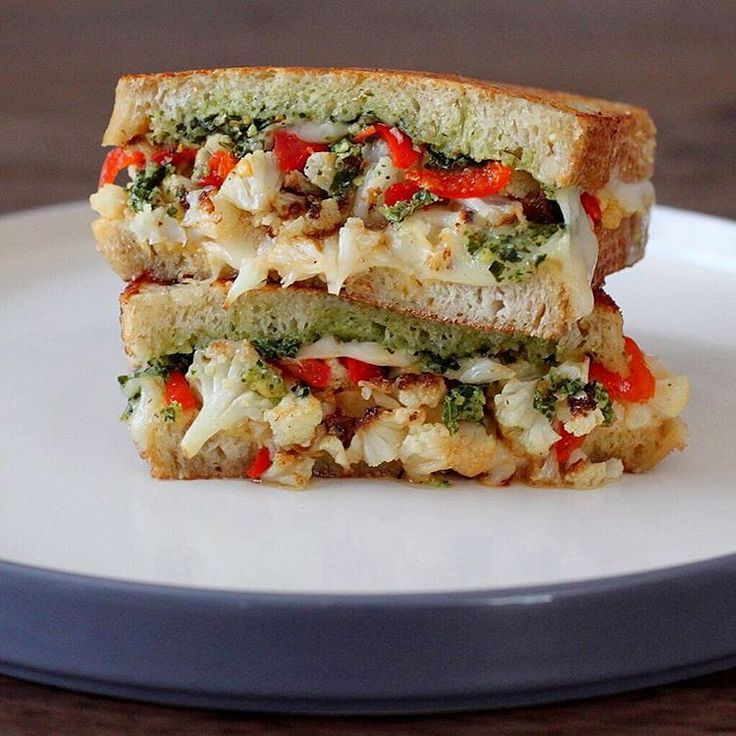 """Festive snacks for 1: Roasted cauliflower grilled cheese w/ smoked provolone, house-pickled peppers, collard green-pistachio pesto and roasted garlic…"""