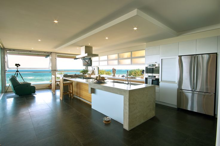 Modern Industrial Style Beach House on the Sunshine Coast. Interiors by Minka Joinery. The kitchen has concrete and Bianco Marble benchtop, cabinetry is finished in Blackbutt and hand laid Anodized Aluminium Sheeting. Overhead doors are Blum Aventos HF with  acrylic inserts.