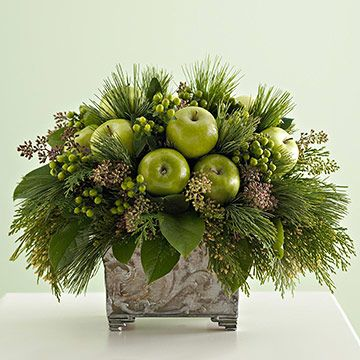 The sheen of apples looks great with seasonal greenery. Place a block of florist's foam in a planter or vase. Add greenery, then fill in with a few apples and berry sprigs for a finishing touch.