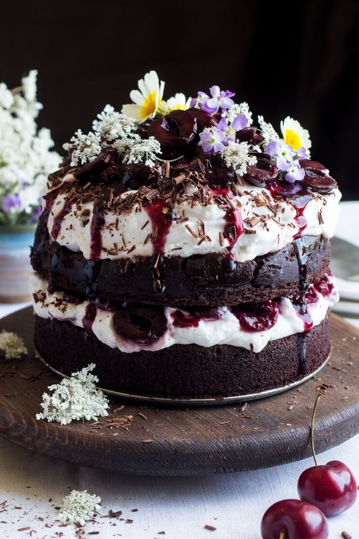 Vegan black forest cake is a show stopper - fluffy cream and drunken cherries sandwiched between tiers of moist chocolate cake. Gluten-free option included.