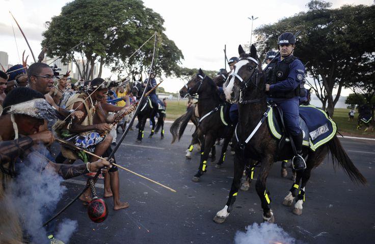 Polisi Brazil menghadang warga suku asli Brazil yang hendak menuju stadion Mane Garrincha dalam demonstrasi anti Piala Dunia di kota Brasilia.