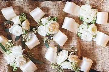 elegant wrist corsages are cuffs of white ranunculus, white majolik spray roses…