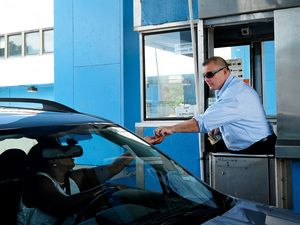 Tollbooth cashier Henry Gregorio collects change from drivers at the New Rochelle Toll Plaza on I-95. Gregorio has worked in a tollbooth since 1980. Tollbooths are gradually being replaced by E-ZPass technology.