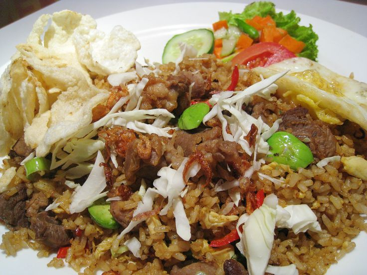 Nasi Goreng (Indonesian style fried rice) with pete or petai (green stinky beans) and goat meat. Also accompanied with fried egg, pickles with fresh slices tomato and cucumber, cabbages, fried shallots, chilli, and emping crackers.