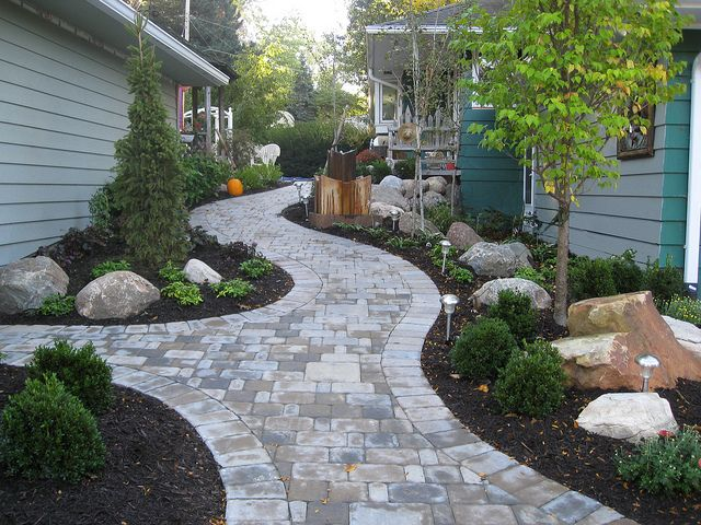 Custom stone pathway between house and garage in Omaha, Nebraska. All work, material and design are from Lanoha Nurseries in Omaha, Nebraska. Featuring boulders, Nebraska trees and custom designed stone pathway built to last through Nebraska winters and summers.