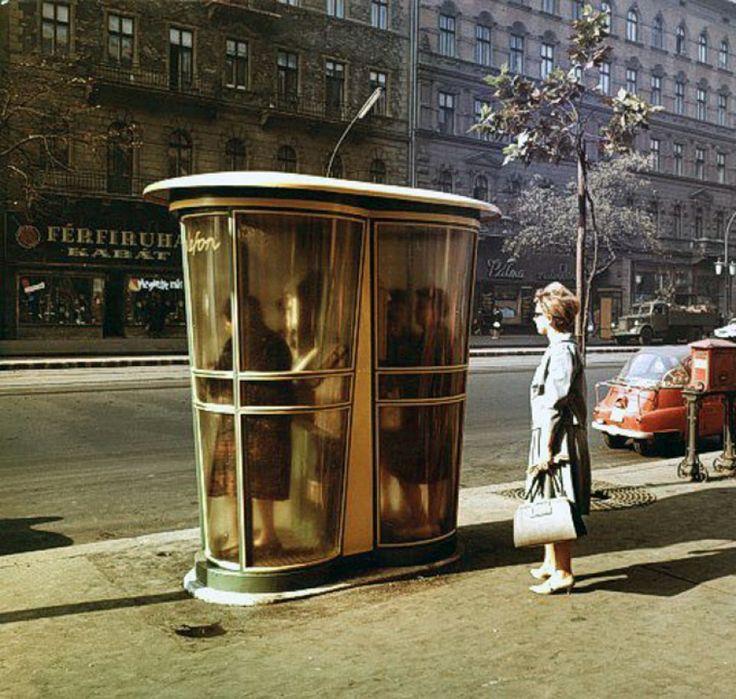 1965, Lenin (Erzsébet) körút. Bánk elnevezése szerint az új telefonfülke. Az én elnevezésem szerint: műanyag telefonfülke. Még így, a műanyagon át is látszik, hogy ez még tantuszos...Nyugalom, a tantusznak semmi köze a tetanuszhoz...Mindez a Madách színház előtt. Színes, szélesvásznú, magyarul beszélő, 3D, Quadro, stb. kivitelben. Na jó..., ezen utóbbi mondat nem minden állítása igaz. A háttérben a Pálma cukrászda. Hja kérem, akkor még nem 300 forint volt egy gombóc fagyi, mint később…