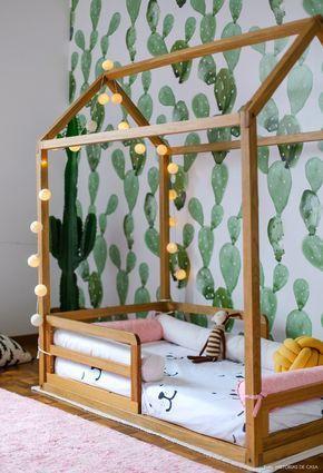 Quarto infantil tem papel de parede com estampa de cactos, tapete rosa e cama no formato de casinha.