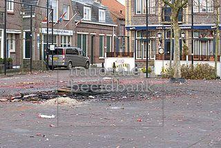 Resten van een vreugdevuur en vuurwerkafval op het dorpsplein van het Zeeuwse dorpje Hoek