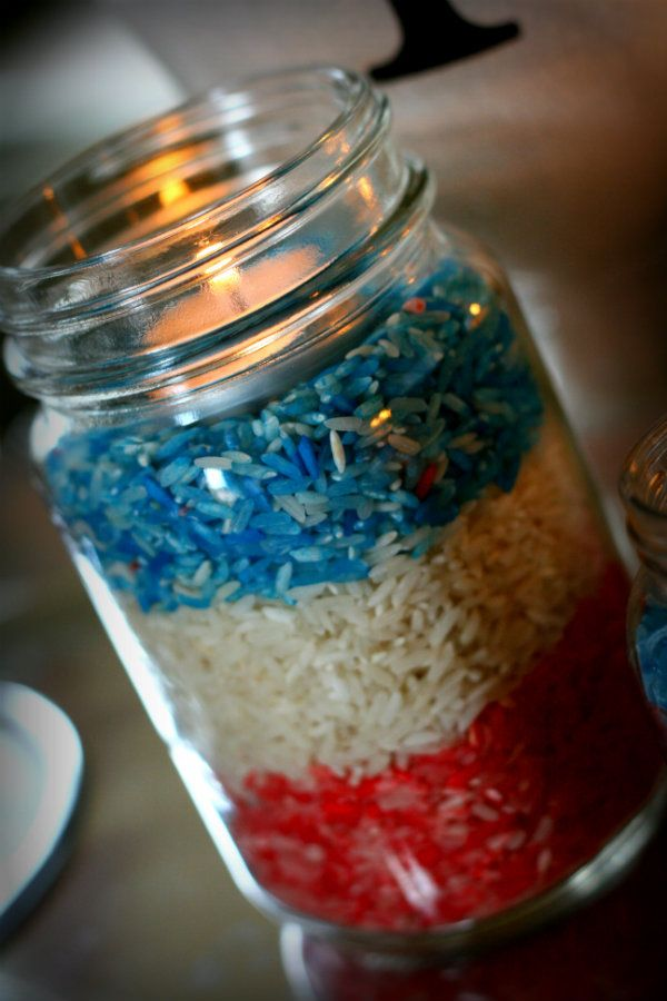 Pour the rice in a glass bowl, drop a few drops of food coloring right on the rice and mixed until well blended.  Once blended, pour into jars by color. Add a tealight. Done!