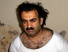 Bedraggled man with heavy chest hair and tousled hair wearing a white t-shirt-Khalid Sheikh Mohammed.
