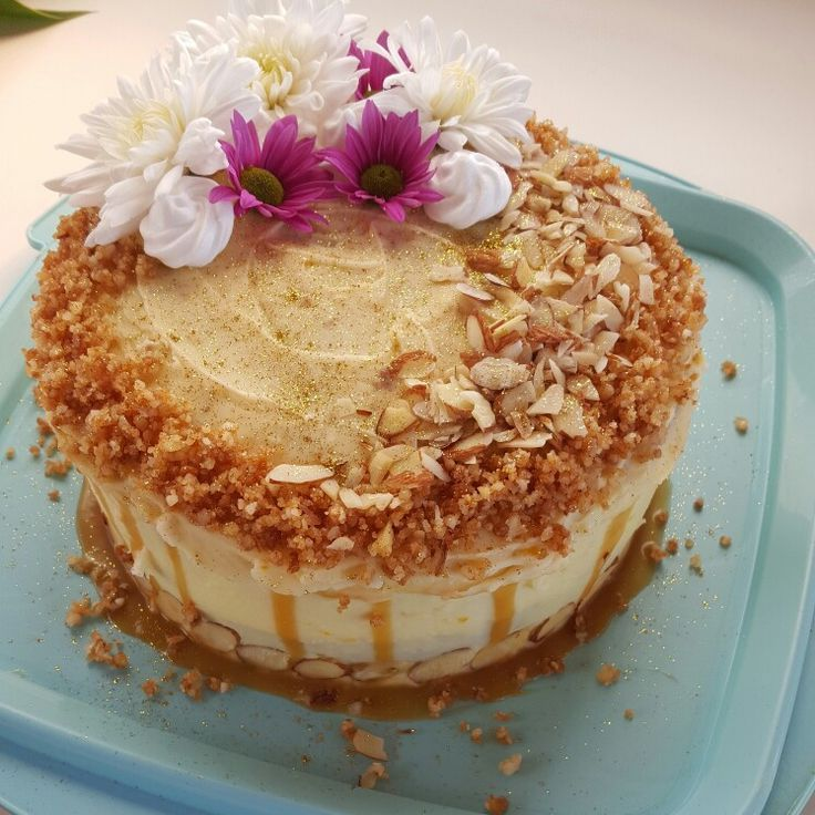 Carrot cake with vanilla cream cheese icing,  salted caramel sauce,  salted caramel macadamia crumb and sliced almonds topped with beautiful fresh flowers and mini meringues