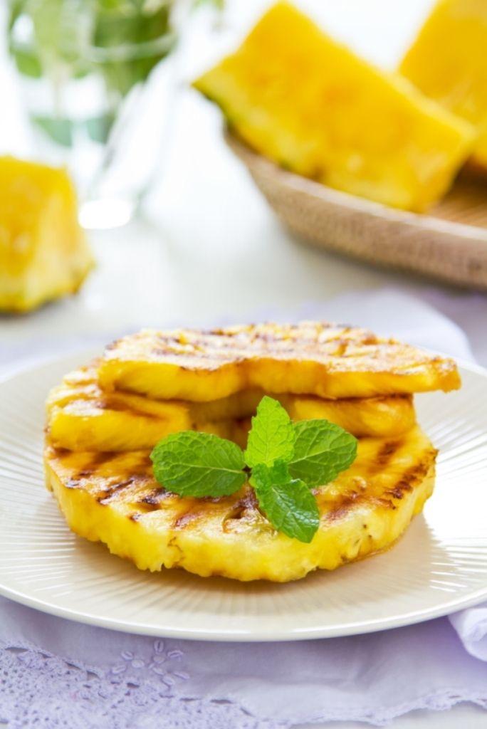 Bereiden: Dep de ananas in de suiker, gril goudbruin op de bbq en bestrooi met de kokosrasp. Werk af met basilicum en munt en rasp de chocolade erover. Serveren: Serveer de ananasschijven samen met een bolletje vanilleijs.