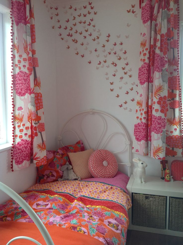 Sleeping corner with a wall of butterflies in soft orange, red, and pinks. Vintage iron bed... More homemade cushions and curtains.