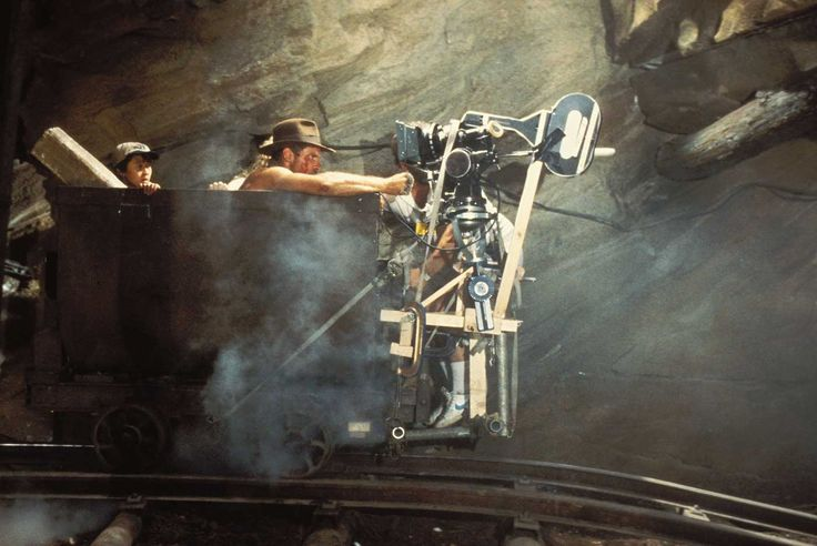 Jonathan Ke Quan, Kate Capshaw and Harrison Ford filming the mine cart scene in Indiana Jones and the Temple of Doom.   Jonathan Ke Quan, Kate Capshaw and Harrison Ford Jonathan Ke Quan, Kate Capshaw and Harrison Ford filming the mine cart scene in Indiana Jones and the Temple of Doom.