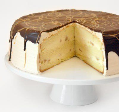 Vanilla cake filled with banana custard and topped with peanut butter buttercream, a layer of chocolate ganache and a peanut butter sauce drizzle.