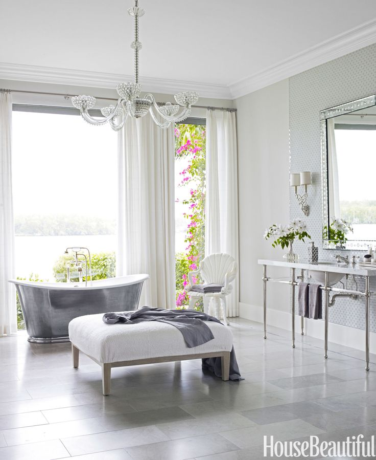 """""""I love a glamorous bathroom,"""" designer Marshall Watson says. He turned the master bath in a Florida house into a spa-like oasis with floor-to-ceiling windows, a Waterworks cast-iron tub, a custom vanity with crystal bars, also by Waterworks, and a crystal chandelier from John Salibello. Walls are Silver Satin in Aura by Benjamin Moore.   - HouseBeautiful.com"""