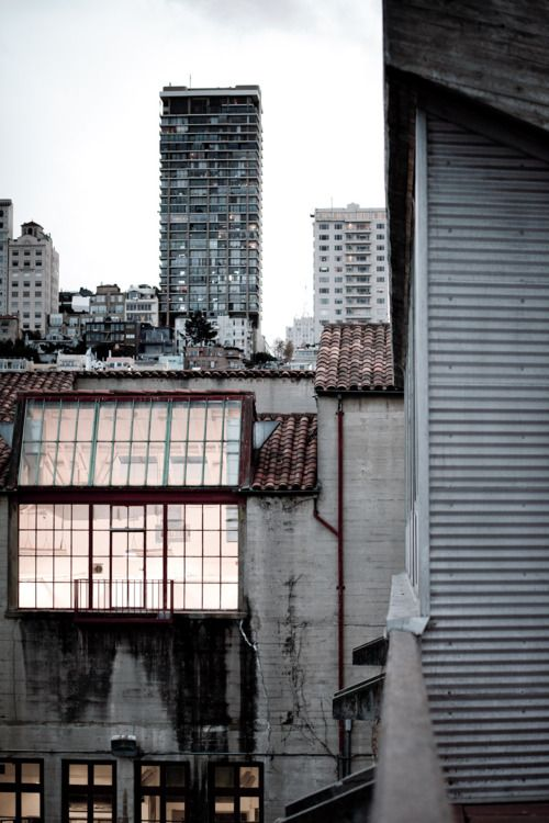 This image is a great example of  industrial city design. The massive warehouse window and the city smog, the mixed with grey tones and the building that show years of industrial wear, the most visible being the black and soot-stained walls after many years of exposure.