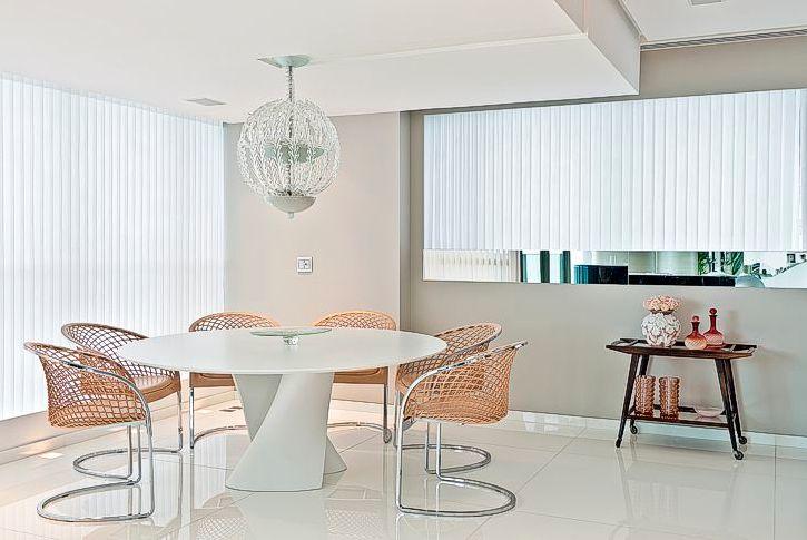 Sala de jantar com peças super diferentes, como a mesa oval branca da Montenapoleone + cadeiras Areta de Franco + luminária de cristal. Projeto Santos e Santos.