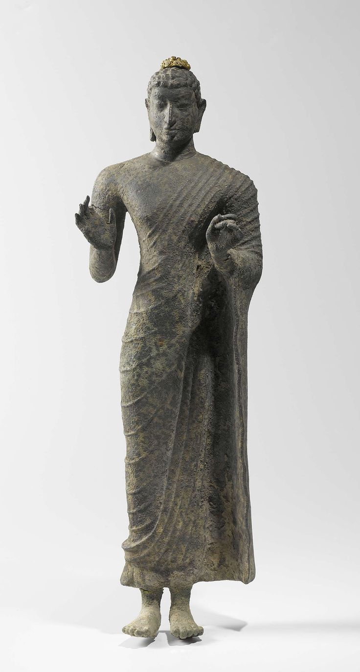 Standing Bronze Buddha . 700- 800 CE. bronze, h 42.0cm × w 12.0cm. Although this figure was found on Java, it was probably made elsewhere and exported to Indonesia. The drapery folds of the monk's robe are characteristic of Buddha figures from India or Sri Lanka. The (ushnisha), or pro-tuberance on the head, a standard feature in representations of the Buddha, is a later addition in gold.