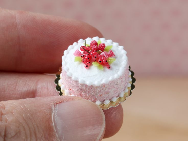 Pink pastel miniature cake decorated with red fruit and berlingot candy