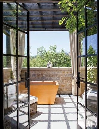 On the master bath terrace of Gisele Bündchen and Tom Brady's former home in Los Angeles, curtains of a Perennials fabric can be drawn to shade a hinoki-wood tub  | archdigest.com