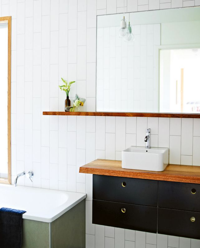 Bathroom: Small sink, black & wood, ledge, frameless mirror, and vertical subway tile