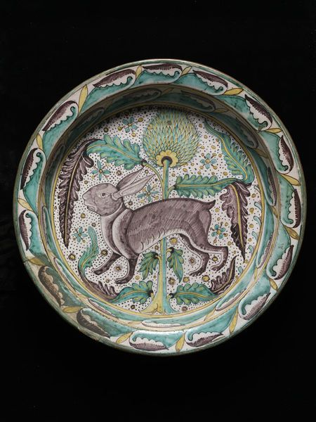 Large basins have been depicted in Italian paintings and manuscripts in scenes of dining and cleansing. Washing hands prior to dining and during the meal itself was a standard custom in 15th century Italy. This dish, or basin, may have been used for washing and then kept on display on a sideboard to show off its fine decoration. The basin is covered with a tin-opacified glaze which gives a bright white covering on which the design is painted. This type of decorative glazing is known as maiol