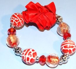 Armband met glas-, metallook-,  metaal- en porseleinen kralen en satijn, elastisch.