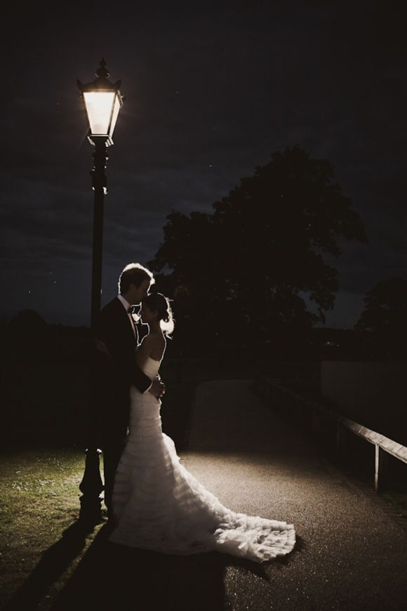 Bride and groom under a street lamp at night by Cathi-d