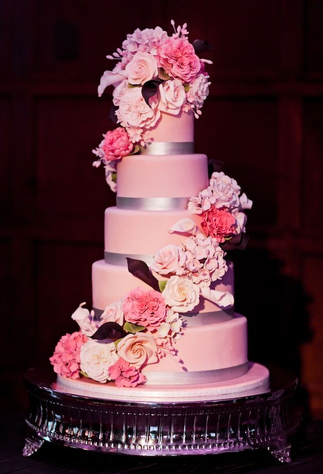 The couple's tall wedding cake featured five blush tiers embellished with silver ribbon detail and sugar flowers crafted to match those blooms used in reception centerpieces. #WeddingCake Photograph by: Heather Waraksa Photography. Read more: https://www.insideweddings.com/weddings/great-gatsby-inspired-spring-wedding-in-new-york/363/.