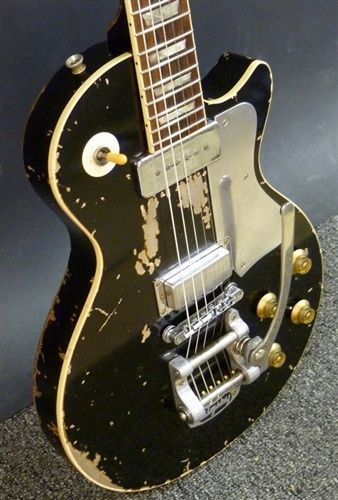"""Neil Young's """"Old Black"""": a Gibson Les Paul Goldtop, painted black with one original P-90 pickup and one mini-humbucker from a Gibson Firebird. It has an updated Tune-O-Matic bridge, an aluminum pick guard and a Bigsby B-7 vibratto tailpiece. He received the guitar in a trade with Jim Messina in 1969, for an orange Gretsch 6120 Chet Atkins model hollow body."""
