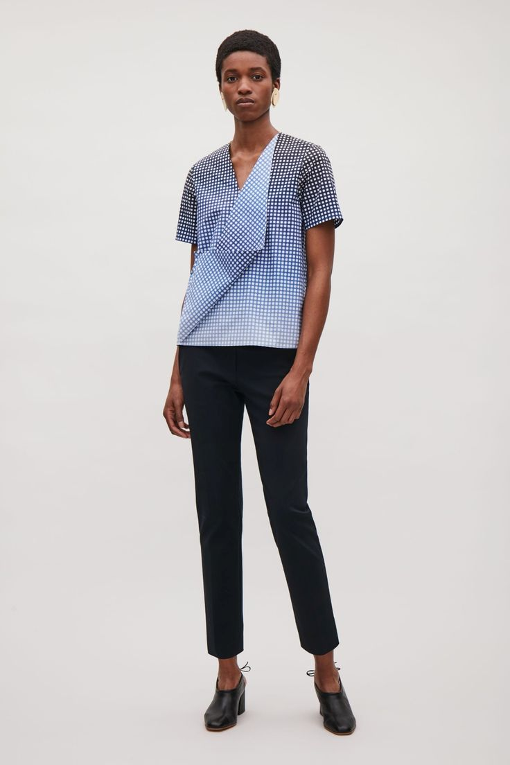 Made from a soft cotton poplin, this top has a abstract drape detail at the front that fastens with a subtle press button. A boxy fit, it has a deep v-neckline, short sleeves and simple, pinned finishes.