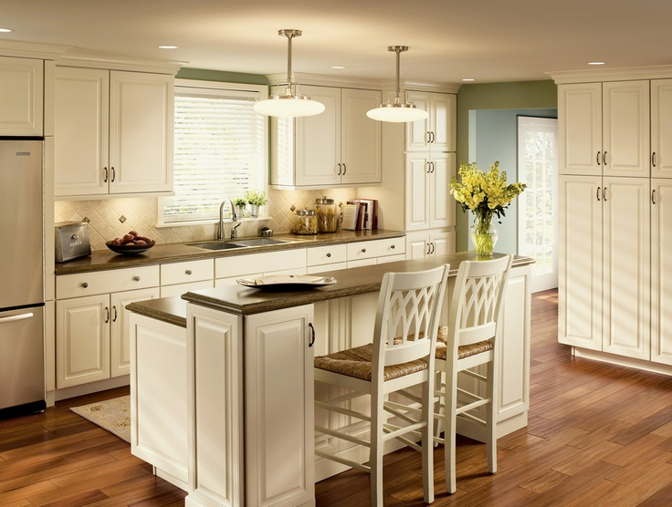 Cove molding and square raised door panels add architectural interest to this bright and spacious kitchen in cream Thermafoil.