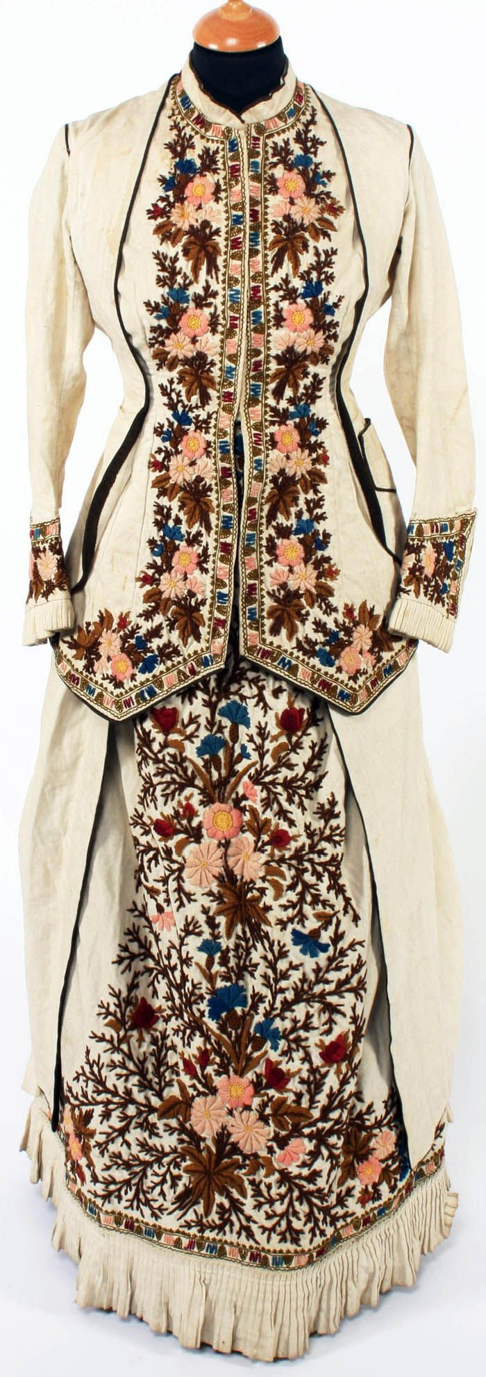 An 1880s embroidered day dress of cream cotton, with bustle skirt and long-sleeved bodice, decorated with dense floral woolwork in brown, blue, and pink down the center front and at the cuffs. Bonham's