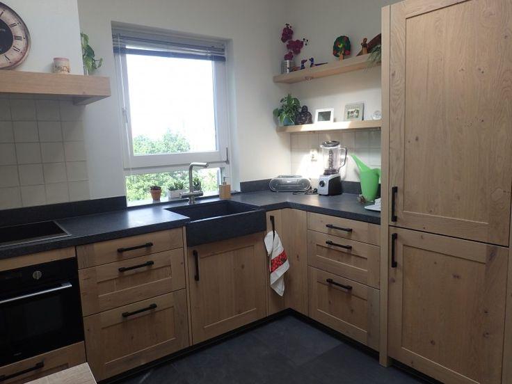 Houten keuken met granieten werkblad en spoelbak. zwarte apparatuur en grepen voor het contrast