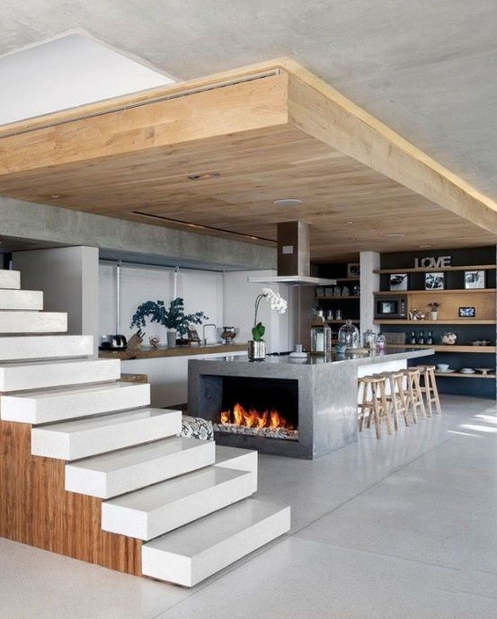 Modern kitchen island with fireplace, open stairs and XL overhang. Interesting design.
