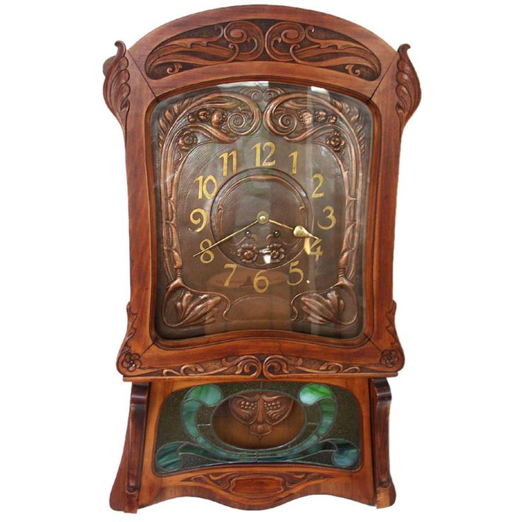 French Fruitwood Art Nouveau Wall Clock  France  Early 20th Century  Lovely wall clock in the Art Nouveau style. Carved fruitwood frame, with the whiplash floral flourishes that define the style. Hammered copper faceplate, with applied brass numerals and hands. Lower panel with leaded glass panes, conceals the hammered copper pendelum. The works are restored and full functional, includes winding key.