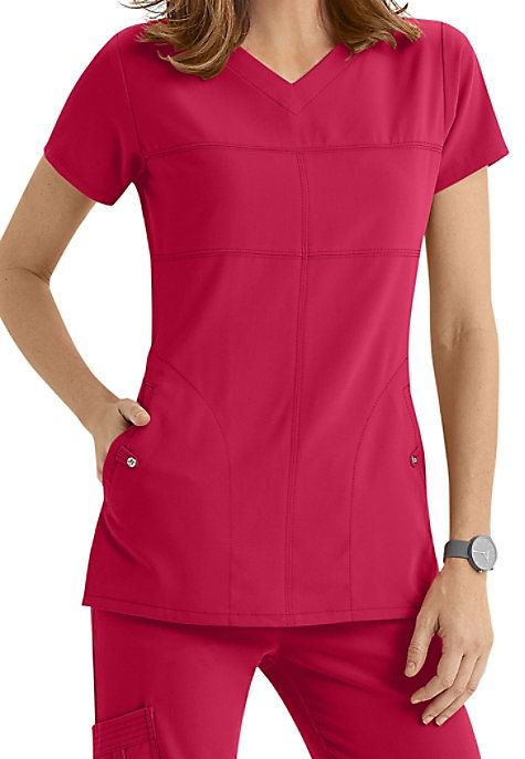 TIME TO CHANGE IT UPYou'll satisfy your urge for something different with this Grey's Anatomy scrub top and its innovative cut, tiny button accents, and fitted tailoring.  The fabric stretches when you do, and two perfectly-sized pockets keep your phone, pens, and other necessities in easy reach.   Grey's Anatomy Signature 2 Pocket Soft V-neck Scrub Tops  V-neck  Fitted back  Four way stretch  Two welt pockets  71% polyester/ 24% rayon/ 5% spandex  Medium center back len...