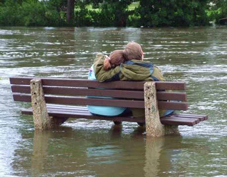 Young lovers sitting on bench in the middle of a flood - Photo By: Jo Parsons