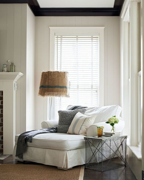 A crab trap side table and a lamp—both from a local boutique—bookend this sitting area's Shabby Chic chaise lounge.