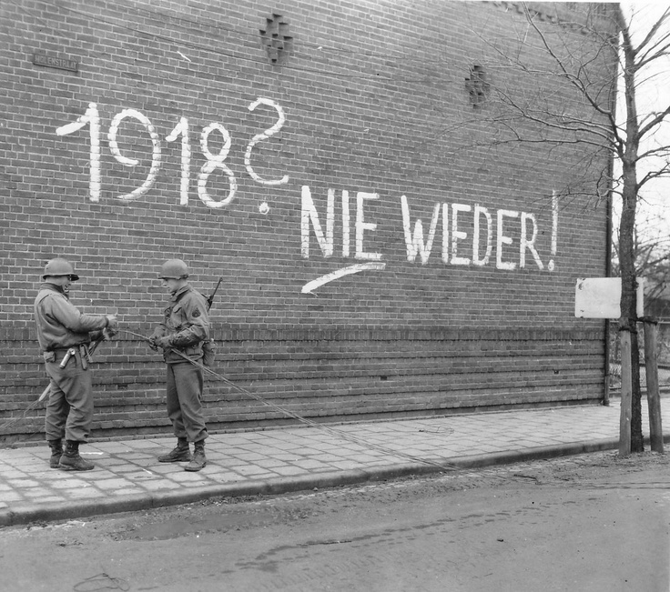"""Somewhere in Germany, Feb 1945: US Army technicians work on telephone wiring. The graffiti behind them reads: """"1918? Never Again!"""" referring of course to the German defeat in WW1."""