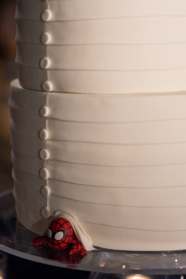 Have something like the groom's favorite character (like this Spider-Man!) peeking out of your pretty wedding cake.