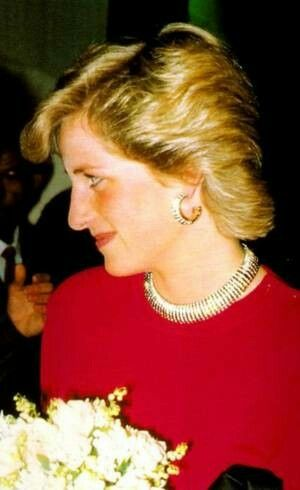 May 06, 1987: Princess Diana at a Lionel Richie Concert at the Wembley Arena, London. Wearing a red dress and spiraled gold necklace and matching earrings.