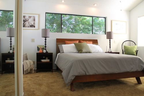 In the master bedroom, a calming color scheme of gray, green and brown with bits of orange prevails, echoing the leafy scene outside the windows. With B&W nature photography on the walls and tall lamps with gray lampshades, this bedroom is just begging to be napped in :).